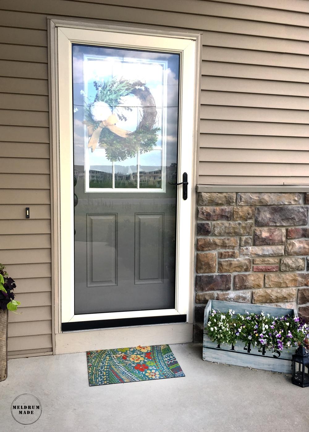 Final front door - black trim storm door and handle, fresh grey paint, black door handle, pretty wreath.