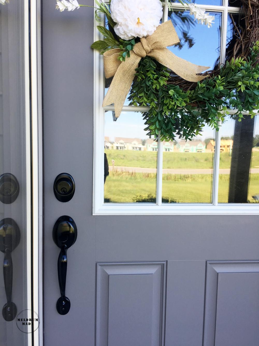 Final front door - fresh grey paint, black door handle, pretty wreath.