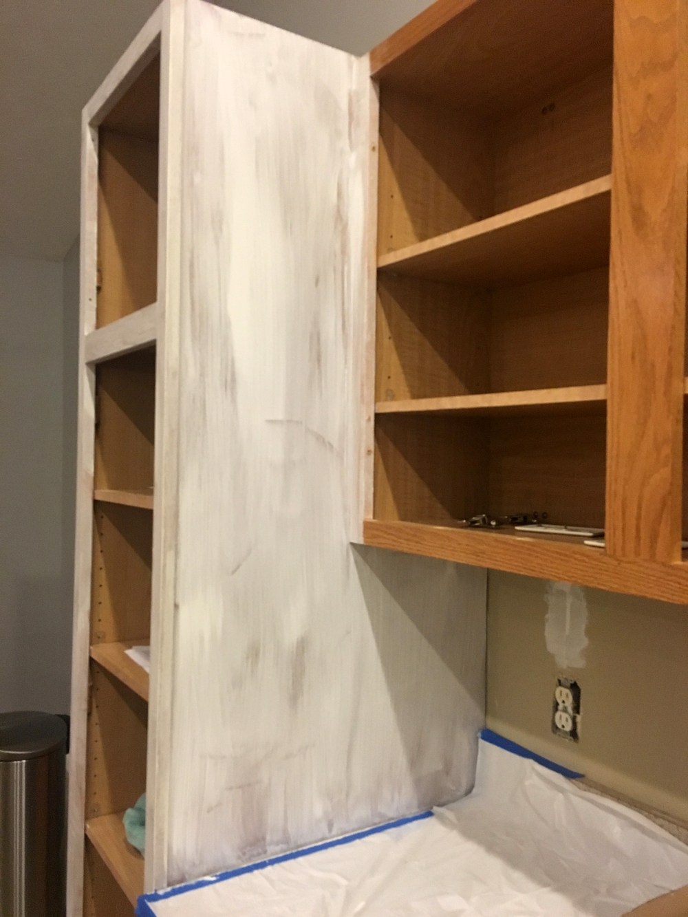 Cabinet with white primer, kitchen renovation, painters tape.