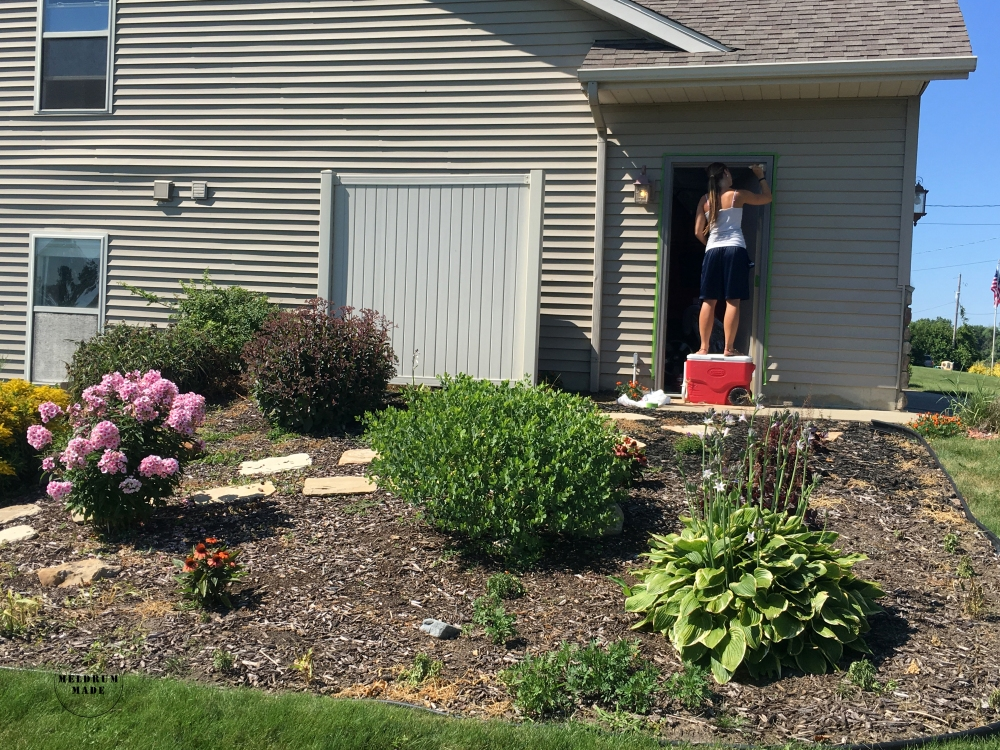 "Jessica hard at work painting the side door - featuring the garden ""before""."