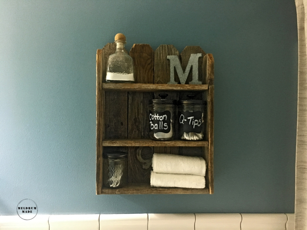 Rustic and charming simple bathroom decor detail. Old bottle with bath salts, rolled washcloths, mason jars with cotton balls, q-tips, and toothpicks.